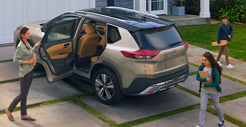 2021 Nissan Rogue in a driveway with door open for family to get in