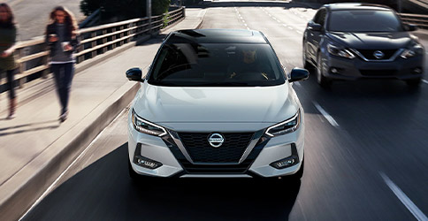 2021 Nissan Sentra front view in white driving through city streets