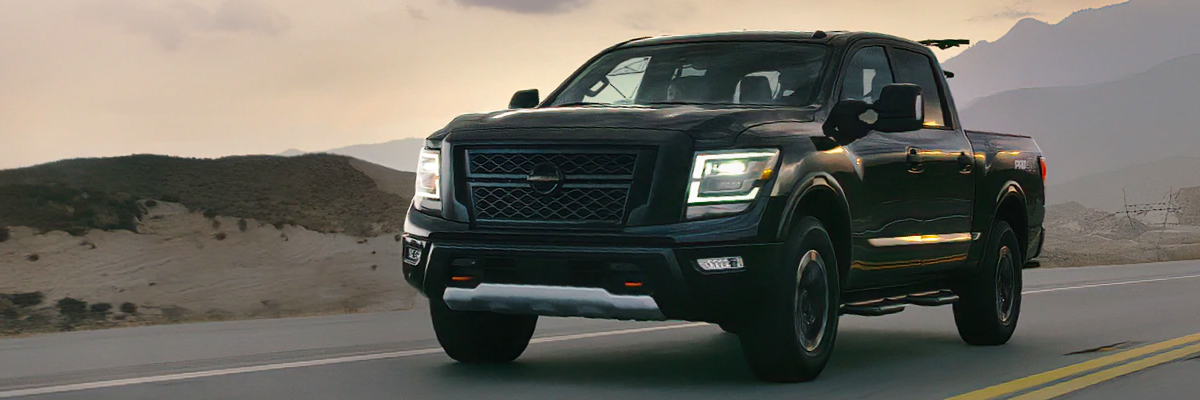 2021 Nissan TITAN Crew Cab in black on a highway at sunset