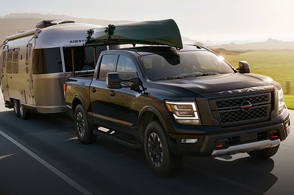 2021 Nissan TITAN on highway with canoe on top and towing an airstream through green hills