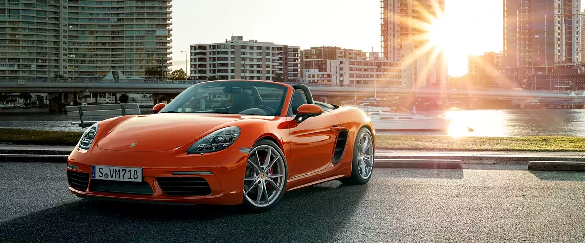 2021 Porsche 718 Boxster parked in front of a body of water with a city in the background