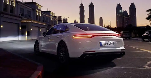 White 2021 Porsche Panamera rear view with headlights on