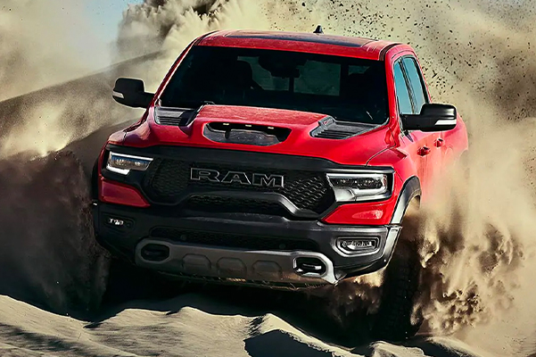 Display The 2021 Ram 1500 TRX being driven over a sand dune, churning up a large dust cloud.
