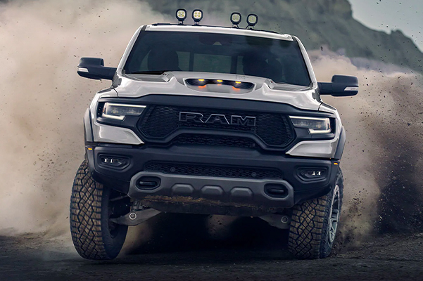 Display A 2021 Ram 1500 TRX being driven toward the camera with a cloud of dust behind it.