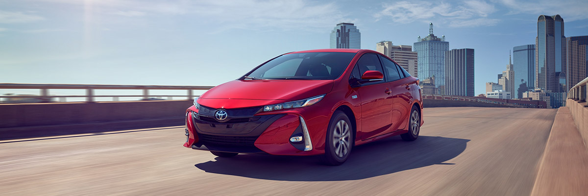 2021 Toyota Prius Prime Limited shown in Supersonic Red front driving on road