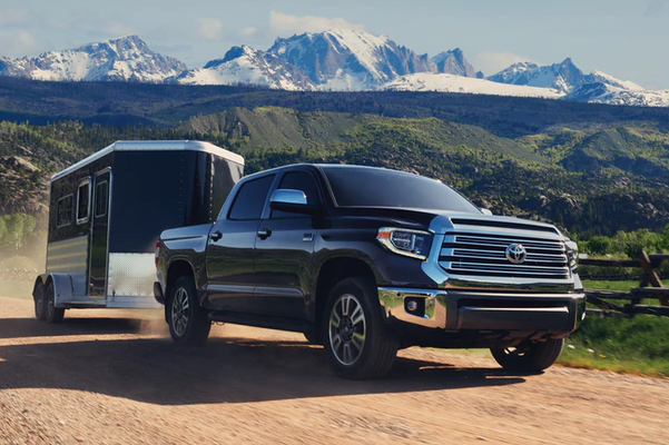 black Toyota Tundra showcasing towing capabilities on a dirt road with snow mountains in the background