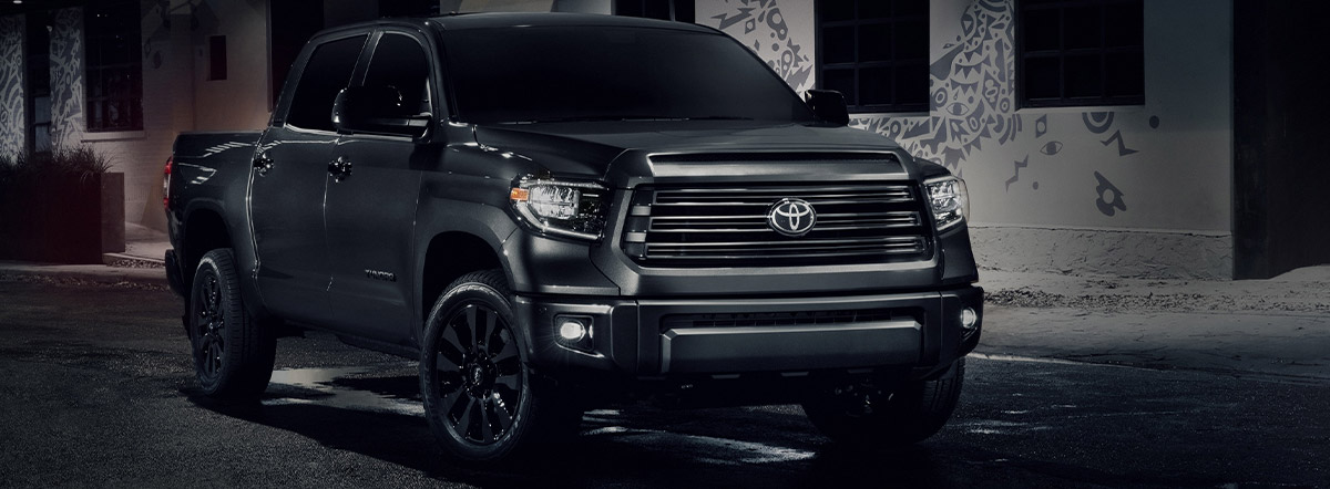 side and frontal view of a black Toyota Tundra truck at night with the headlighst on
