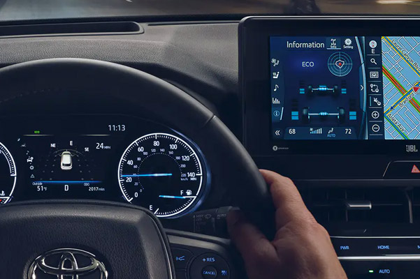 Image of a person driving their 2021 Toyota Venza with their hands on the wheel and touchscreen navigation to the right of them