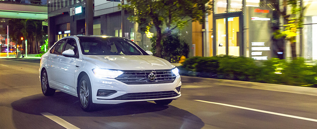 front shot of the 2021 vw jetta driving down the street at night