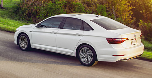 side view of a white 2021 vw jetta driving down the road