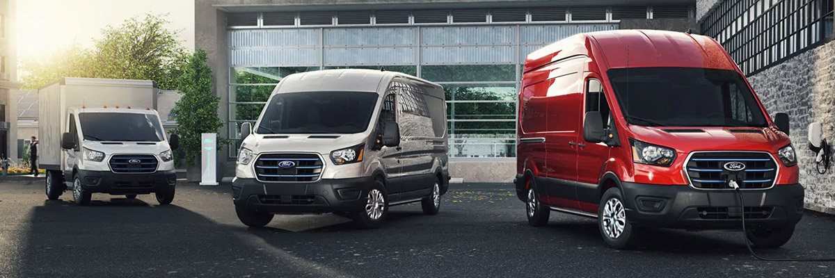 Three 2022 Ford E Transits parked outside an industrial building