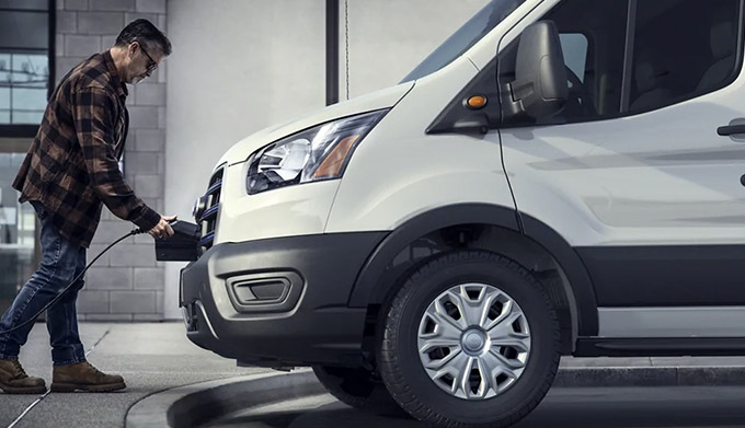 A man plugging a charger into the front of a 2022 Ford E Transit