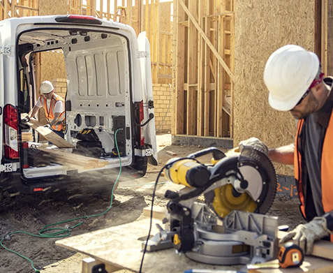 A rear shot of a 2022 Ford E Transit on a construction site with a worker operating a miter saw