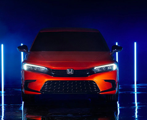 front view of the 2022 honda civic with the headlights on