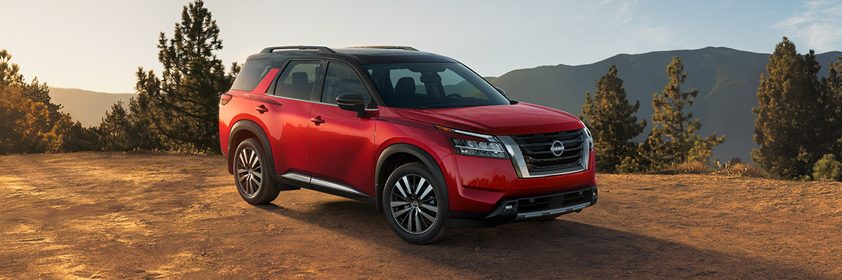 side profile of 2022 Nissan Pathfinder in red color parked on tough terrain with mountains in the background