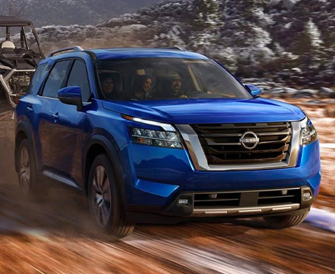 side profile of 2022 nissan pathfinder in blue color towing recreational vehicles on a dirt road with snow.