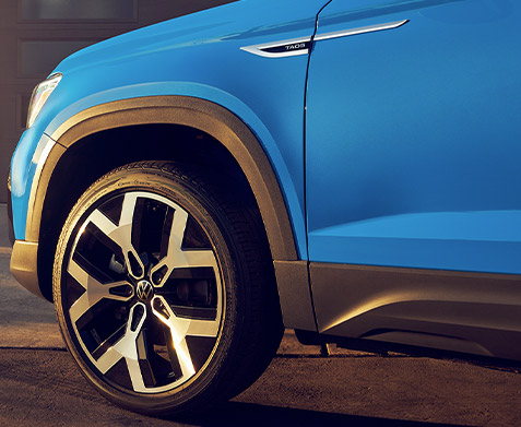 "Taos in Cornflower Blue Metallic, close-up of available 19"" alloy wheels."