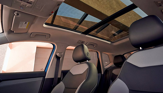 Interior view of Taos front seats in available leather seating surfaces and panoramic sunroof.