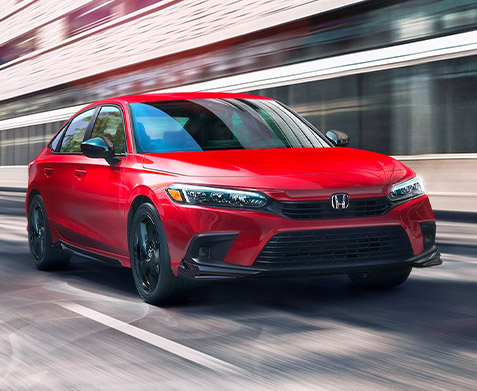 Front driver-side view of the 2022 Honda Civic Sport Sedan in Rallye Red, driving on a city street