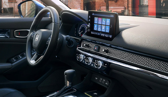 Interior passenger-side view of the steering wheel and dash in the 2022 Honda Civic Touring Sedan with Black Leather.