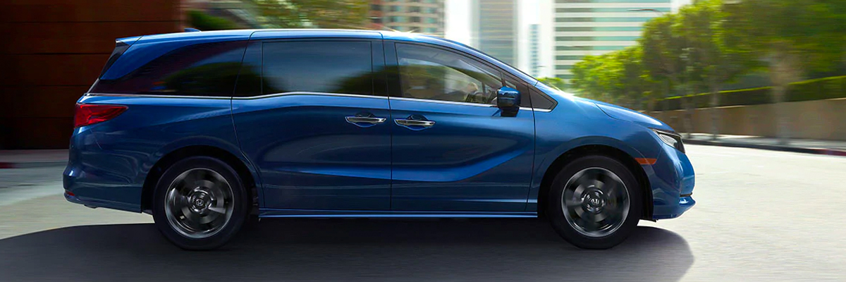 Passenger-side profile view of the 2022 Honda Odyssey Elite in Obsidian Blue Pearl driving in a city environment.