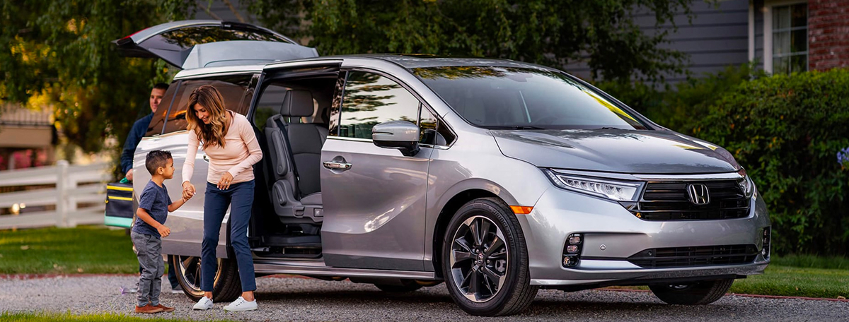 Front driver-side view of the 2022 Honda Odyssey Elite in Lunar Silver Metallic parked in a gravel driveway, with mother and son standing next to the power sliding door.