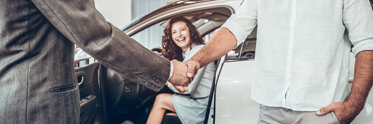 close up of two man closing a deal on a car purchase by shaking hands and woman inside the car smiling in the background
