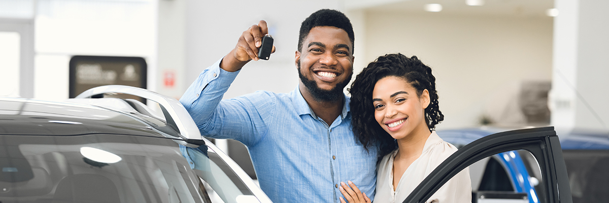 Young woman driving away in first new car