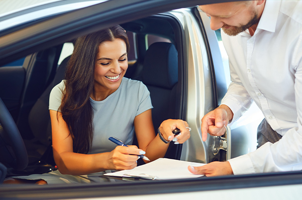 A young woman buys a new car.