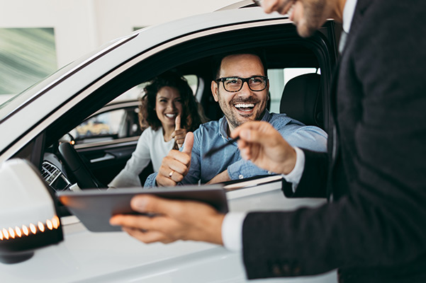 Happy couple in a car with salesman showing tablet
