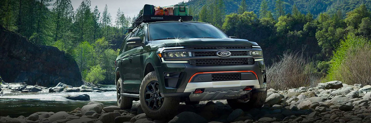 2022 Ford Expedition Timberline in Forged Green Metallic parked on rocks near a river with luggage secured in a roof rack