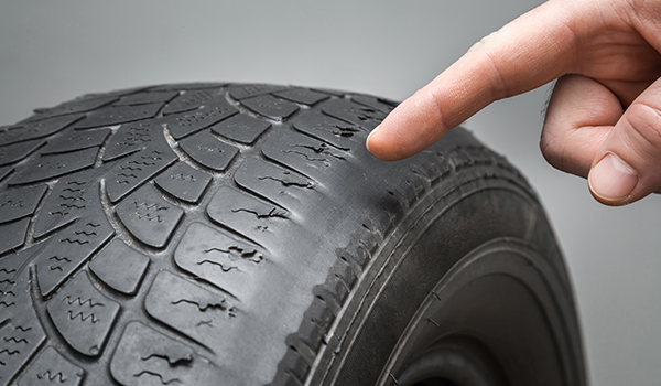 Man's hand finger pointing to the old, damaged and worn black tire tread. Change time. Tire tread problems and solutions concept.