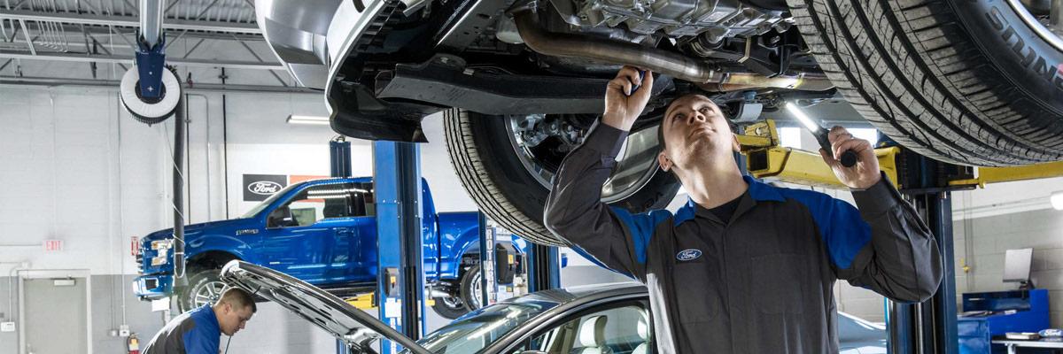 Ford Repair man working on underside of car