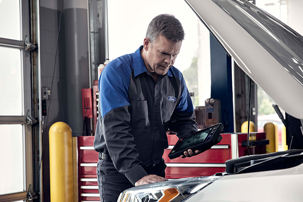 Ford repair man inspecting engine
