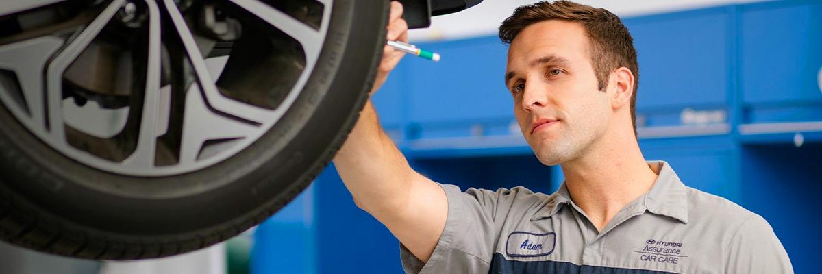 Hyundai technician inspecting tires