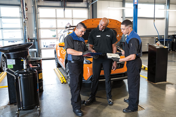 3 service employees talking about a Subaru