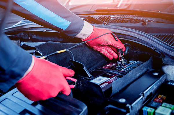 auto technician transferring light current to a car battery