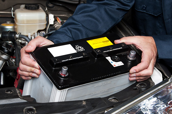 auto technician installing a new car battery on a car