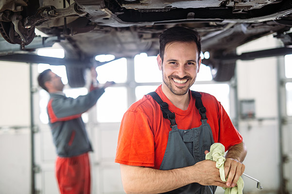 auto technician smiling with red t-shirt inspecting vehicle undercarriage