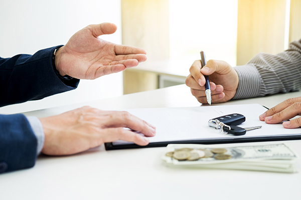 Someone signing paperwork with cash and car keys
